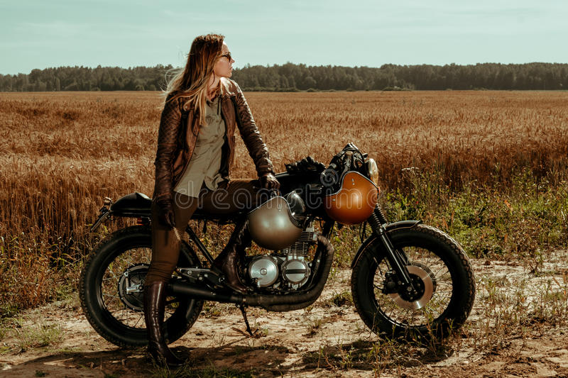 Woman rider with his vintage custom made cafe racer stock photos