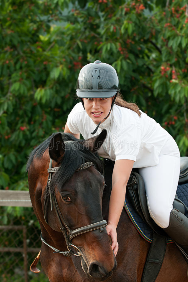 Woman rider and horse. Cheerful young jockey woman ridding with purebred horse outdoors stock images