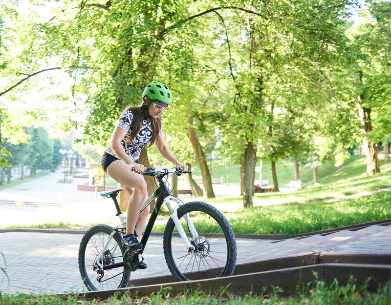 Female cyclist riding bike up paved hill. stock photography
