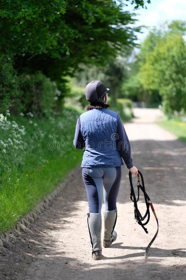 A woman rider in special equipment. And with a horse harness in her hands is walking along the road royalty free stock image