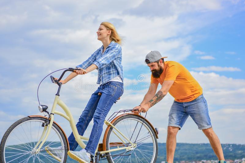 Woman rides bicycle sky background. How to learn to ride bike as an adult. Girl cycling while boyfriend support her stock photography