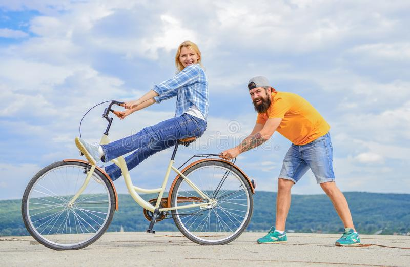 Woman rides bicycle sky background. Man helps keep balance and ride bike. How to learn to ride bike as adult. Girl royalty free stock photos