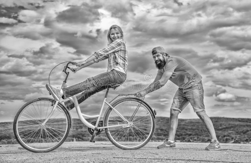 Woman rides bicycle sky background. Man helps keep balance and ride bike. How to learn to ride bike as adult. Girl. Cycling while boyfriend support her. Cycling royalty free stock photo