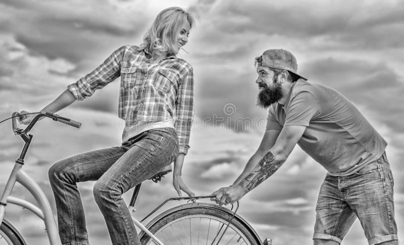 Woman rides bicycle sky background. Service and assistance. Man helps keep balance ride bike. Girl cycling while man. Support her. Support helps believe in royalty free stock photos