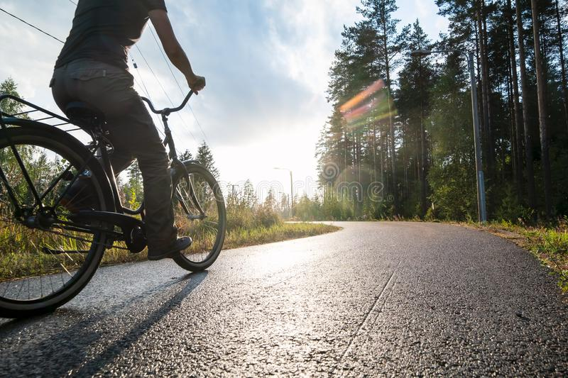 A woman rides a bike on a bicycle path in the rain on a summer evening in the sunshine next to a pine forest. Healthy lifestyle. Concept. Close-up royalty free stock photography