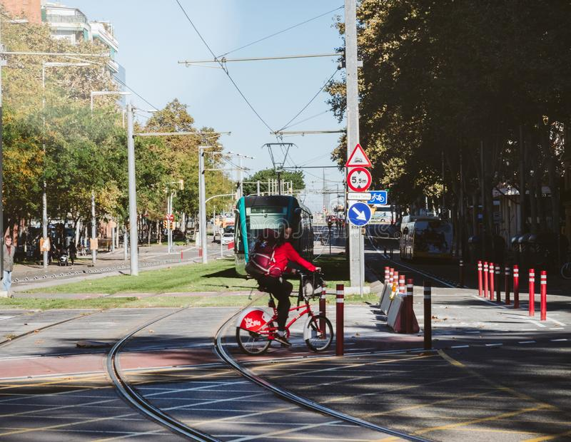 Woman riding bicycle across railroad of tramway Barcelona stock photos