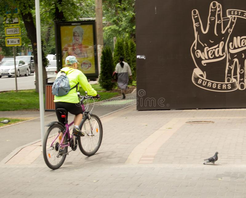 Woman is riding a bicycle along the sidewalk. Almaty, Kazakhstan - 05.23.2018: Tole Bee Street. people in the center of Almaty. Early spring time, people walk stock photos