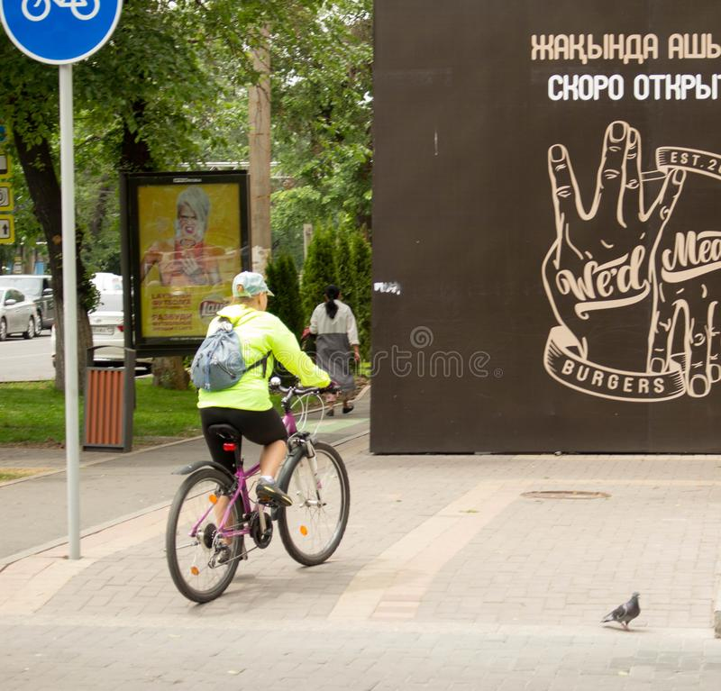 Woman is riding a bicycle along the sidewalk. Almaty, Kazakhstan - 05.23.2018: Tole Bee Street. people in the center of Almaty. Early spring time, people walk.n stock images