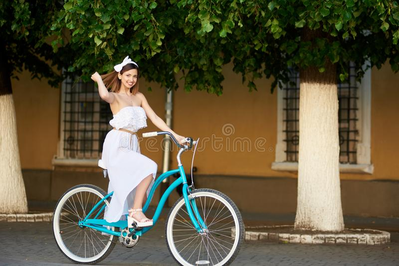 Woman riding on bicycle in city at background trees, walls stock photo