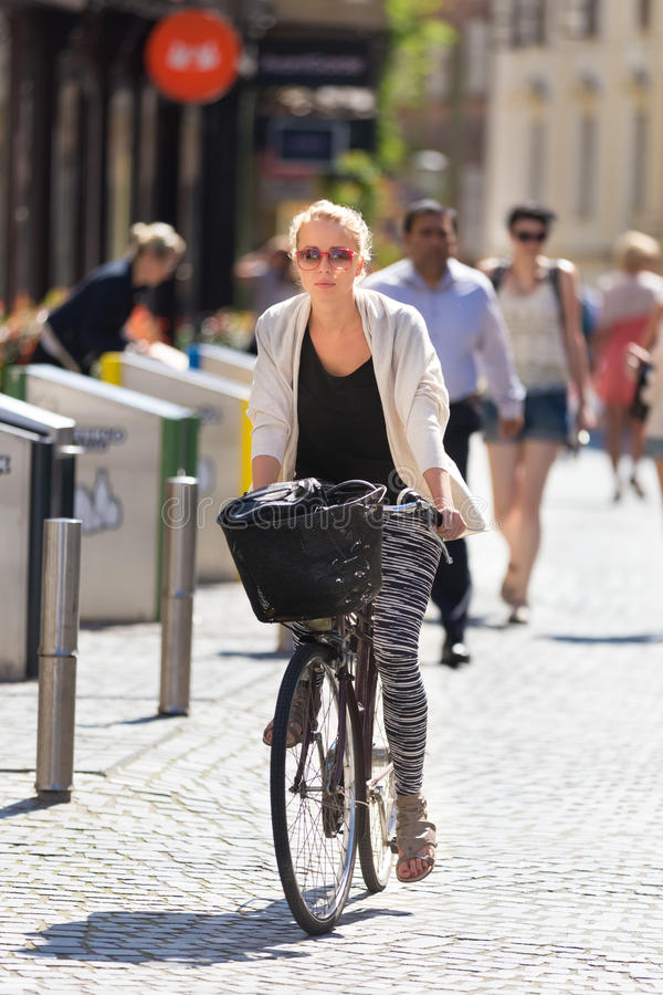 Woman riding bicycle in city center. stock images