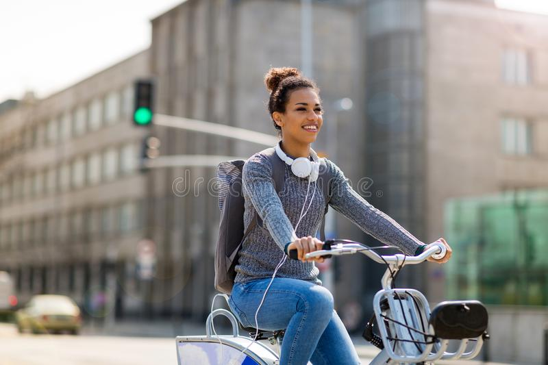 Woman riding bicycle on city street royalty free stock image