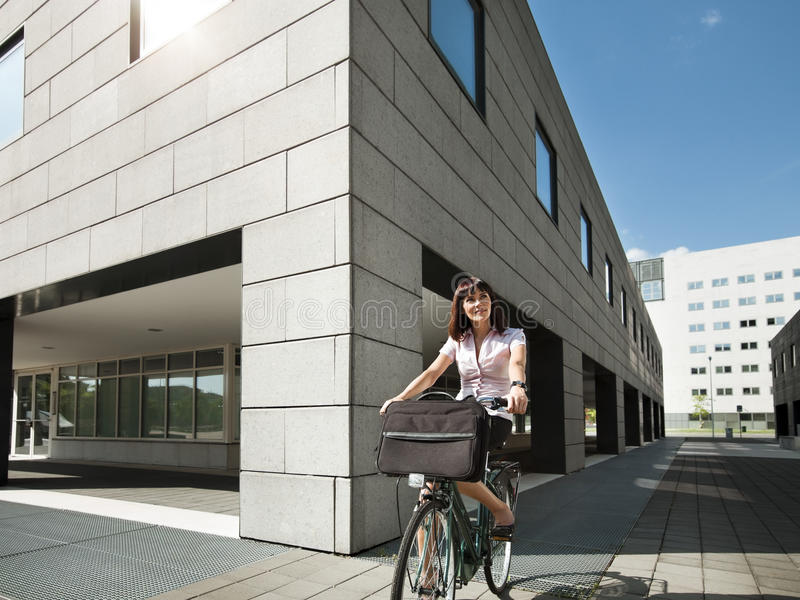 Woman riding bicycle and going to work stock photos