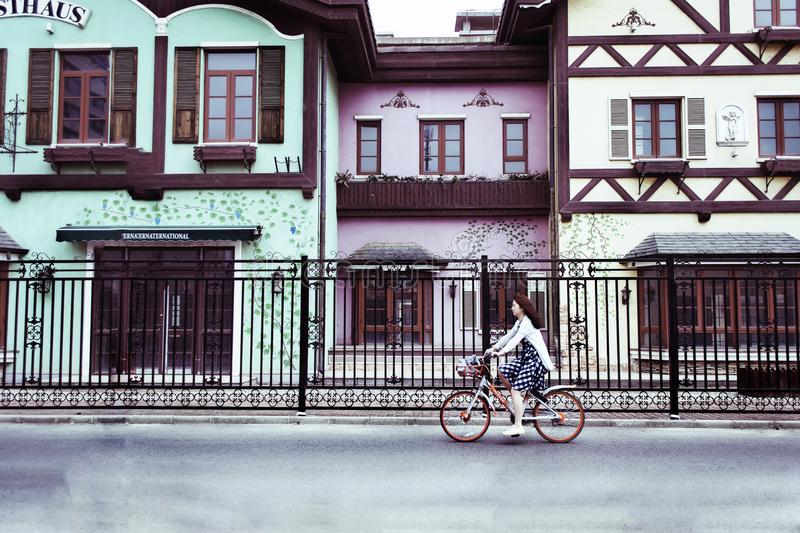 Woman Riding on Bicycle Near Concrete Houses stock images