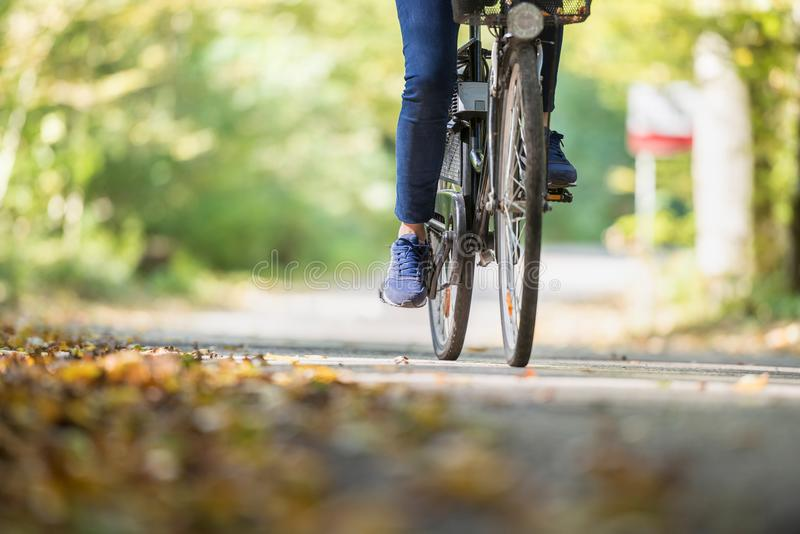 Woman riding a bicycle outdoors on a path in the park stock photos