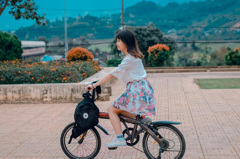 Woman Riding Bicycle Overlooking Orange Flowers and Hills stock photo