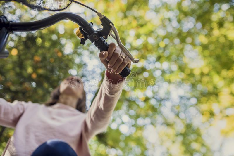 Woman riding a bicycle viewed from below looking up at her hand royalty free stock photos