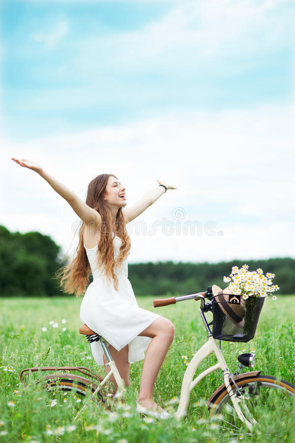 Download Woman Riding Bicycle In Wildflower Field Stock Photo - Image: 25693454
