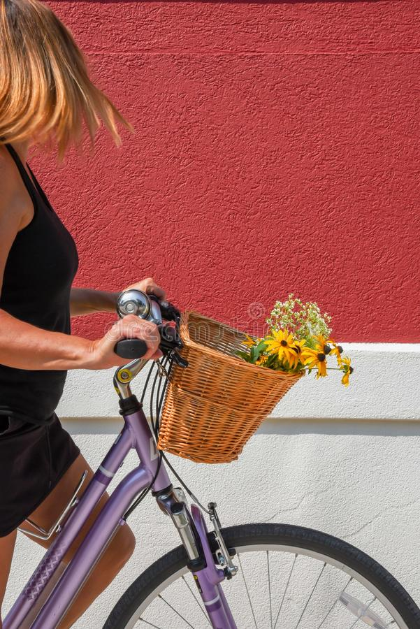 Woman on bicycle against red wall stock photos