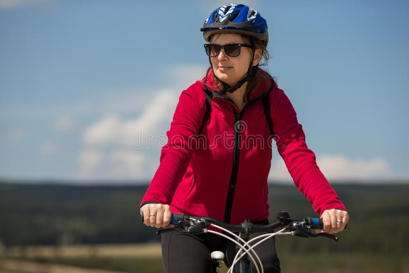 Woman riding bike. In mountains stock photography