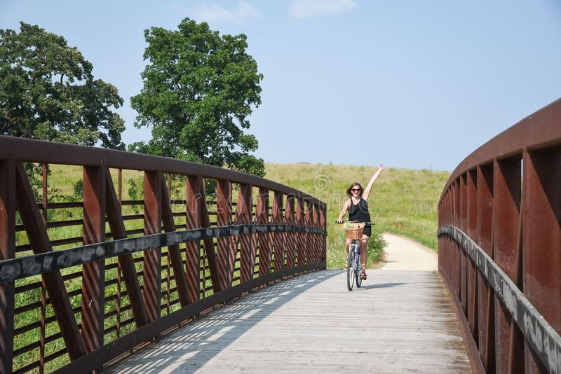 Happy woman riding bike over bridge royalty free stock images