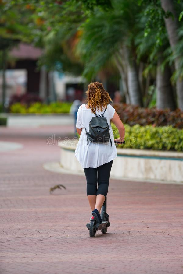 Woman riding a electric scooter on Las Olas Riverwalk stock photos