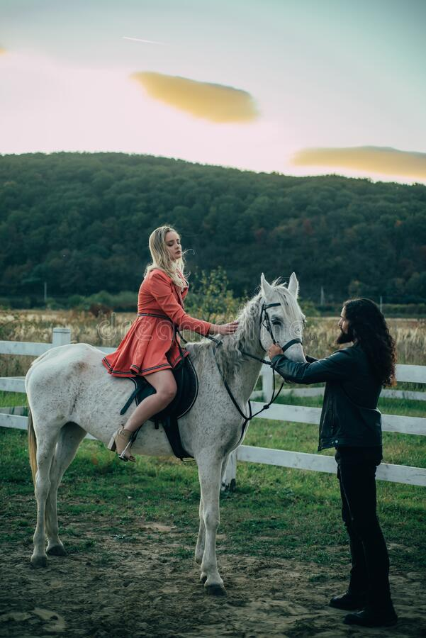 Woman riding grey arabian horse in pink dress. Handsome bearded man driving horse for a bridle and looking at his. Woman riding grey arabian horse in pink dress royalty free stock photo