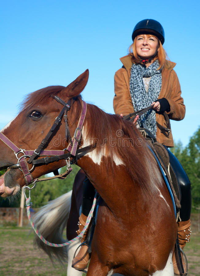 A woman riding a horse royalty free stock images