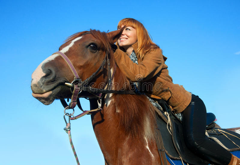 A woman riding a horse royalty free stock photography