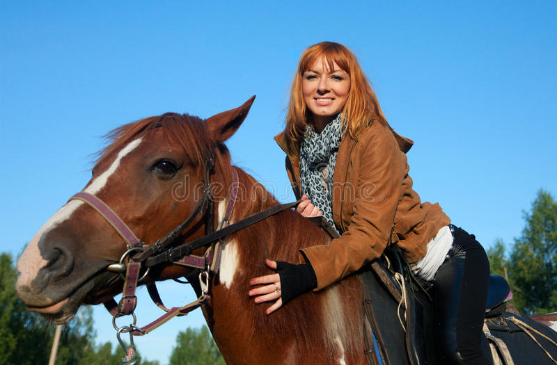 A woman riding a horse royalty free stock image