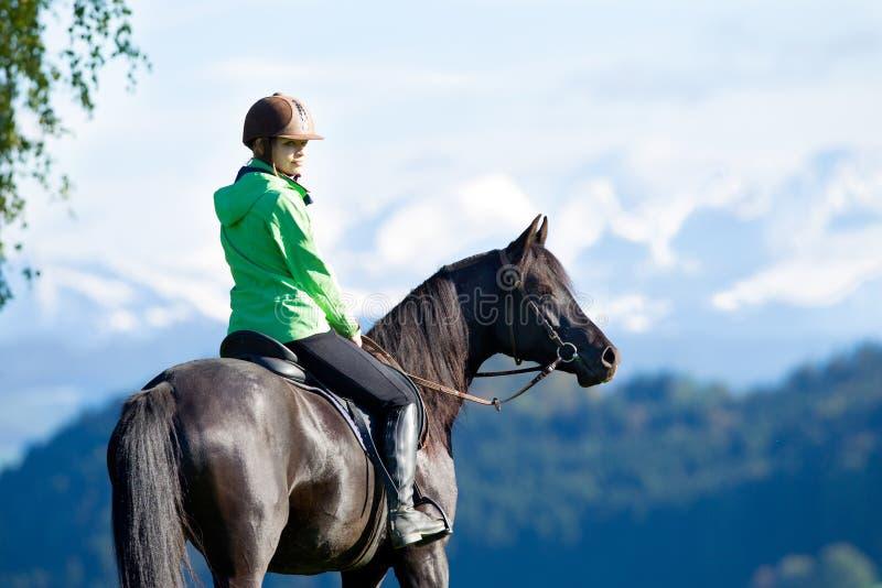Woman riding horse. Woman riding Arabian black horse stock photography