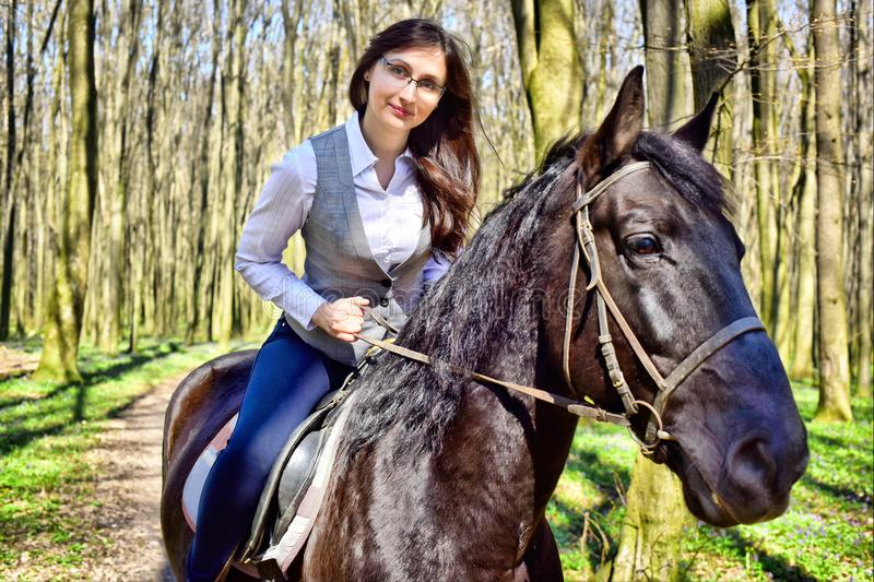 Woman riding a horse in the woods stock images