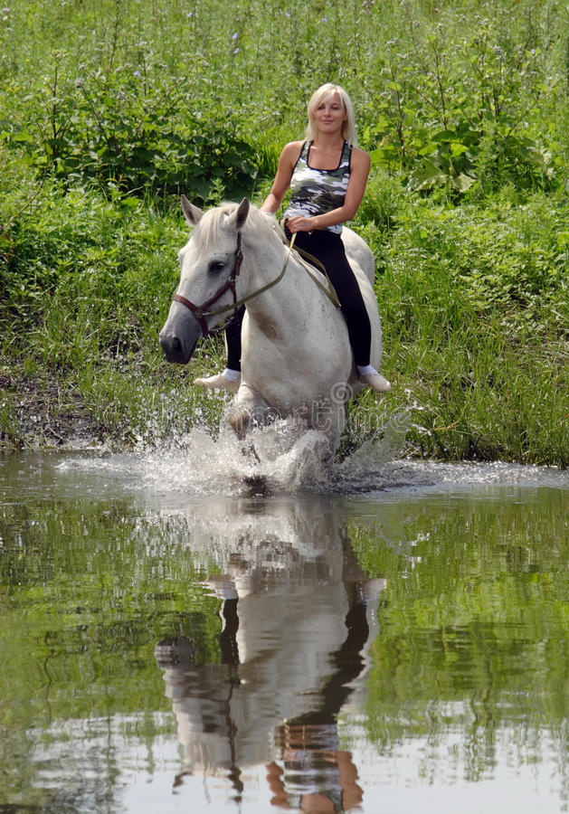 Woman riding horse by rural lake royalty free stock images