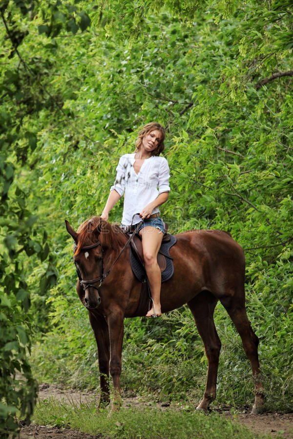 Woman riding horseback through forest royalty free stock image