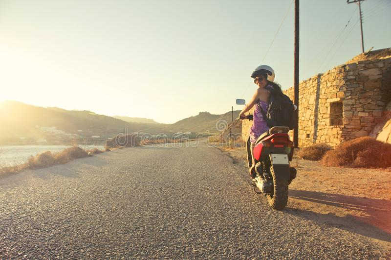 Woman Riding Motor Scooter Travelling on Asphalt Road during Sunrise stock photography