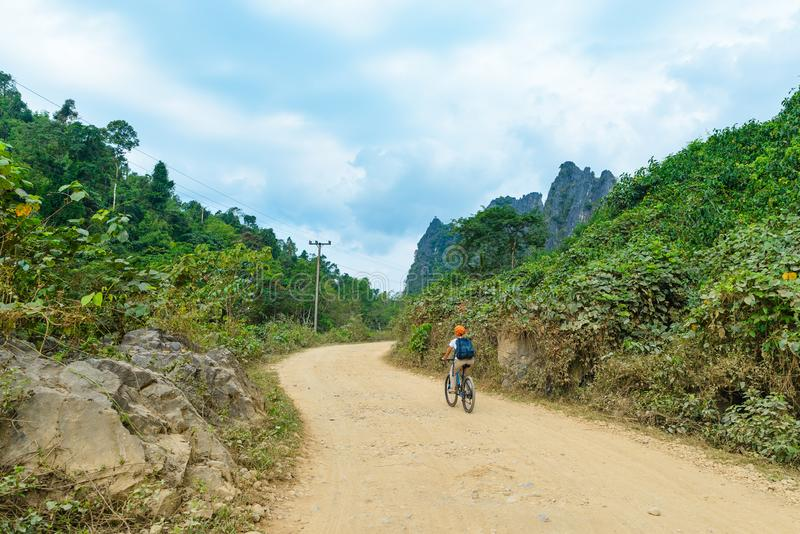 Woman riding mountain bike on dirt road in scenic landscape around Vang Vieng backpacker travel destination in Laos Asia rock royalty free stock image