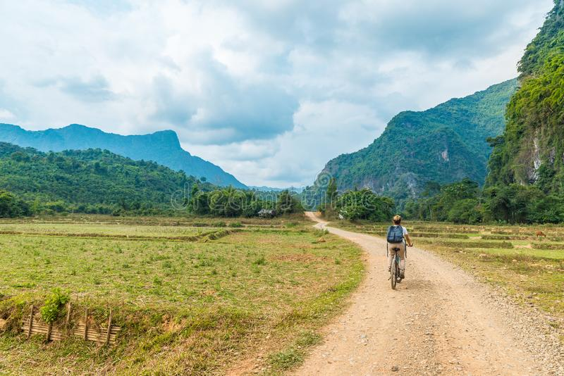 Woman riding mountain bike on dirt road in scenic landscape around Vang Vieng backpacker travel destination in Laos Asia rock stock photo