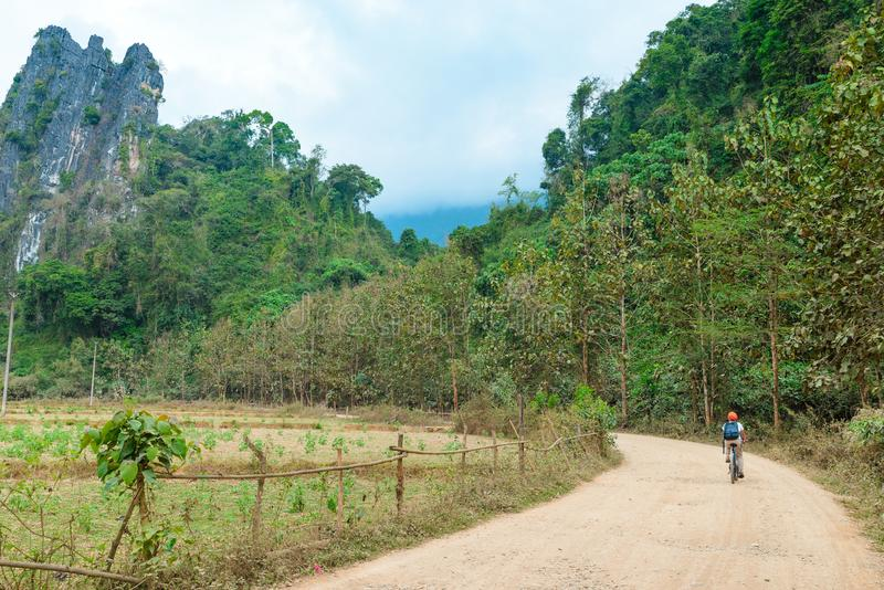 Woman riding mountain bike on dirt road in scenic landscape around Vang Vieng backpacker travel destination in Laos Asia rock stock photography