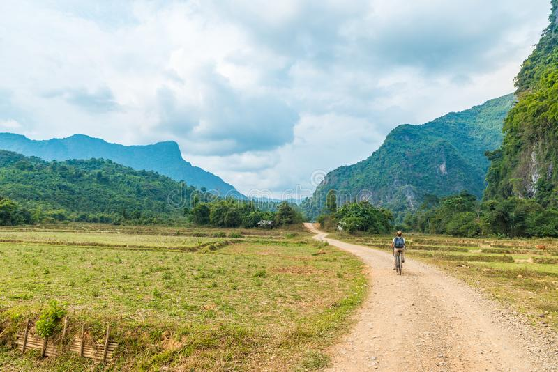 Woman riding mountain bike on dirt road in scenic landscape around Vang Vieng backpacker travel destination in Laos Asia rock royalty free stock photo
