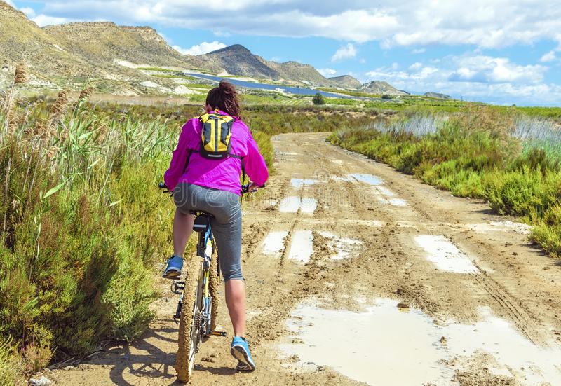 Woman riding a mountain bike by a muddy path of dirt royalty free stock photos