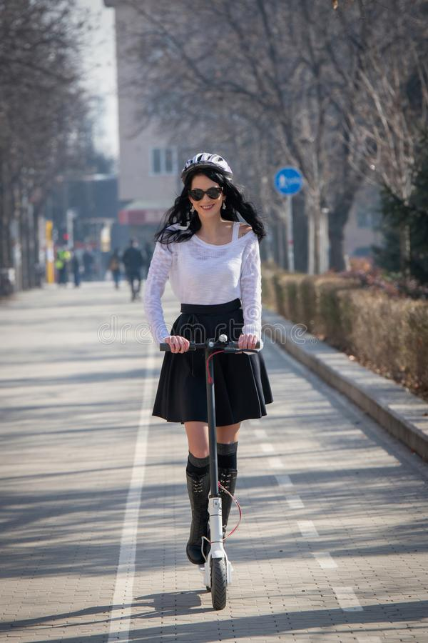Woman riding a scooter. Brunette pushes off the road royalty free stock images
