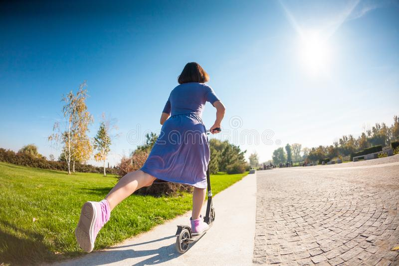Woman riding a scooter. The girl in a dress rides a scooter in the park. Brunette pushes off the road. Feet in sneakers stock photos
