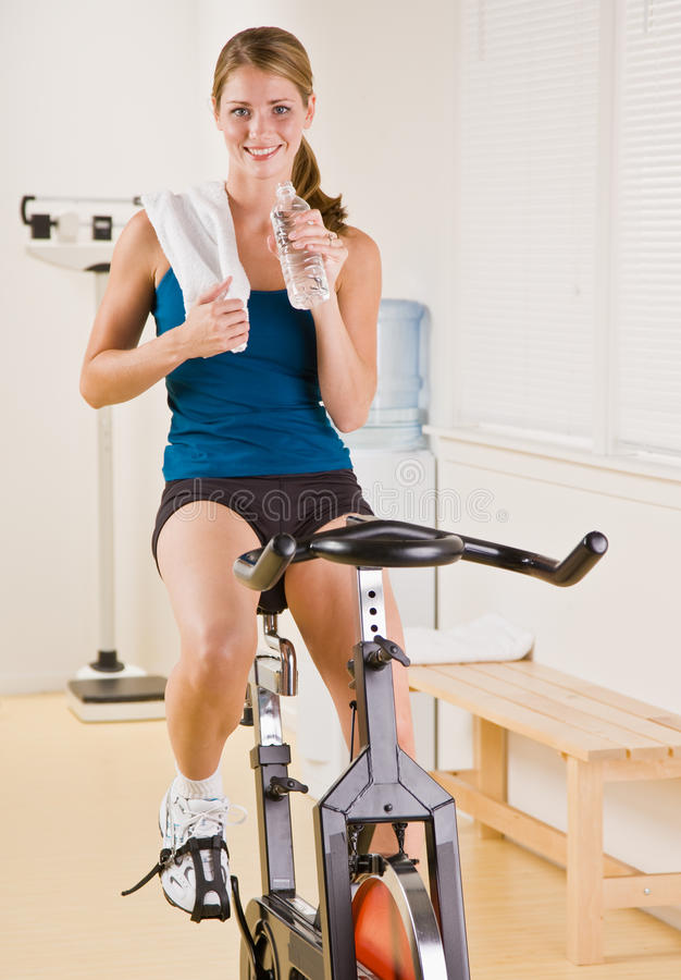 Download Woman Riding Stationary Bicycle In Health Club Stock Photography - Image: 17050622