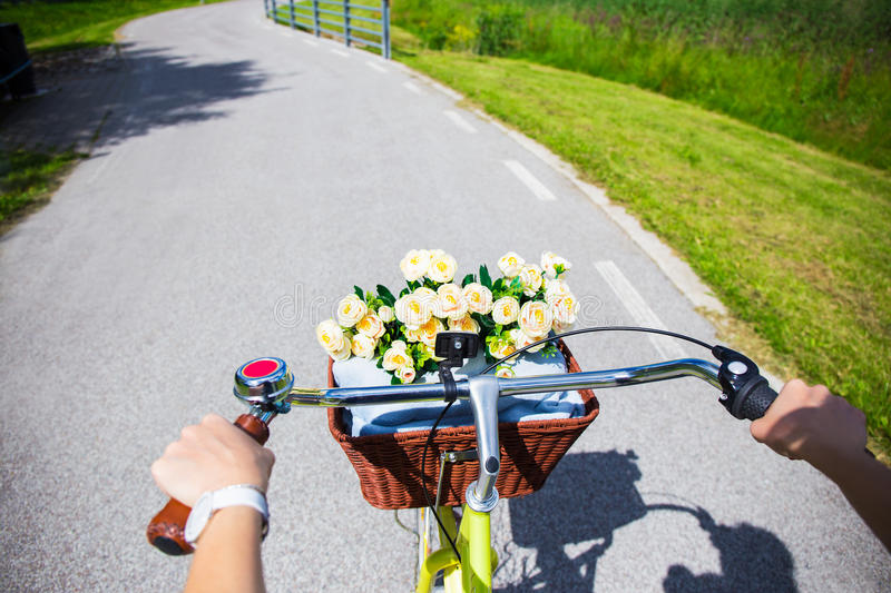 Woman riding vintage bicycle with wicker basket - handlebar view stock photography