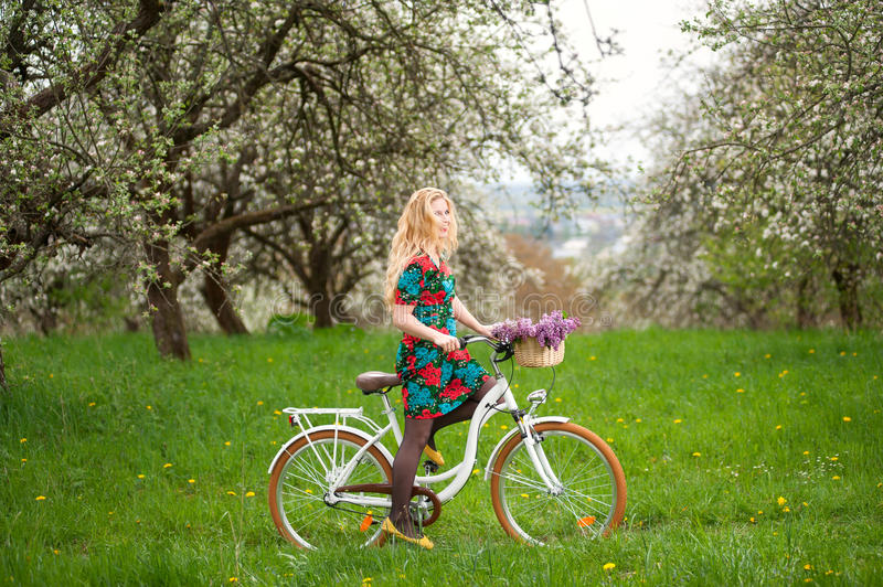 Woman riding vintage white bicycle with flowers basket. Young woman with long blond hair wearing flowered dress riding a vintage white bicycle with flowers royalty free stock photography