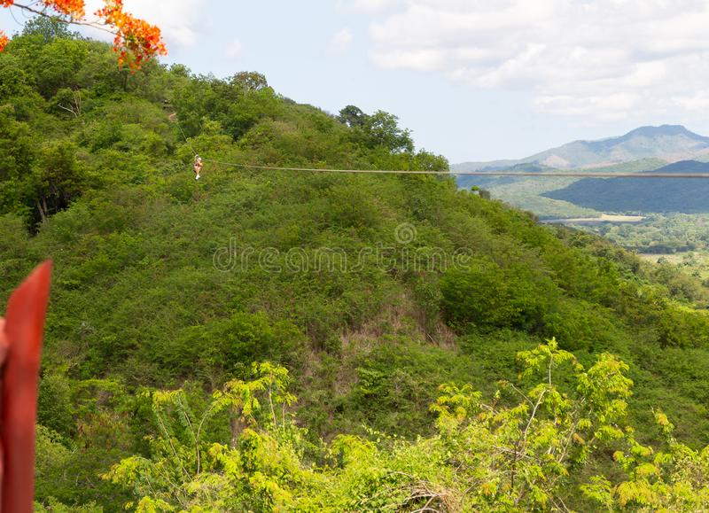 Woman riding in zip line in the Valley of the Sugar Mills in Trinidad Cuba stock image