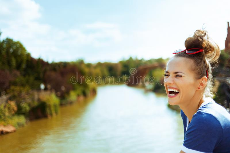 Woman on river boat having fun time while river cruising. Smiling healthy woman in blue t-shirt on river boat having fun time while river cruising stock images