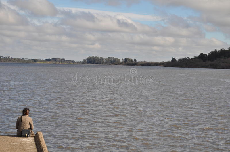 Woman at River. A woman watches the skyline at Rio Negro in Mercedes, Soriano, Uruguay stock image