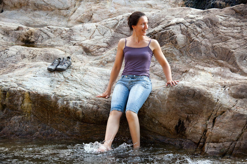 Woman on riverbank. Happy woman seated on riverbank splashing water with foot stock photo