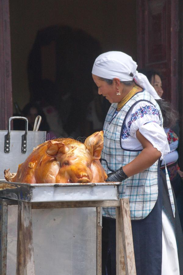 Woman with a roast pig in Cotacachi. Vendor selling roast pig on Day of the Dead in Cotacachi, Ecuador royalty free stock photography