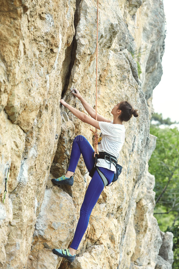 Woman rock climber on the cliff. Young cheerful woman climbs on the cliff. rock climber Learns to climb rocks on a rocky wall. woman makes hard move and looking stock images
